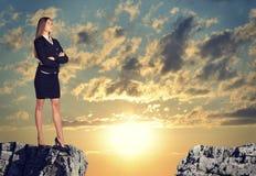 Donna di affari che sta sull'orlo della lacuna della roccia Fotografie Stock Libere da Diritti