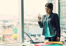 Donna di affari che sta ufficio interno, parlante sullo smartphone e sorridente, buone notizie di udito Fotografia Stock Libera da Diritti