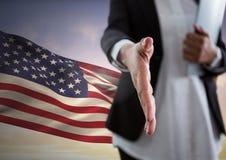 Donna di affari che stringe le mani contro la bandiera americana Immagini Stock