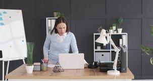 Donna di affari che tiene archivio sullo scaffale e che per mezzo del computer portatile alla scrivania video d archivio