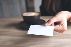 Donna di affari che tiene e che dà un biglietto da visita vuoto a qualcuno con la tazza di caffè sulla tavola immagine stock