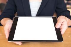Donna di affari che tiene e che mostra un pc nero della compressa con lo schermo da tavolino bianco in bianco sulla tavola fotografia stock