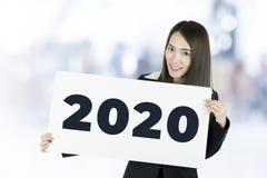 Donna di affari che tiene i cartelli con il segno 2020 immagini stock