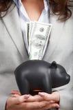 Donna di affari che tiene il porcellino salvadanaio e le banconote in dollari Fotografia Stock