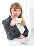 Donna di affari che tiene tazza che si siede allo scrittorio Immagine Stock Libera da Diritti