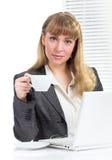 Donna di affari che tiene tazza che si siede allo scrittorio Fotografie Stock Libere da Diritti