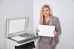 Donna di affari che tiene un foglio di carta e che esamina macchina fotografica fotografia stock