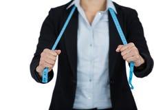 Donna di affari che tiene un nastro di misurazione contro il fondo bianco Fotografia Stock Libera da Diritti
