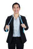 Donna di affari che tiene un nastro di misurazione contro il fondo bianco Immagini Stock