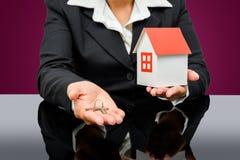 Donna di affari che tiene una casa e una chiave di modello Immagine Stock Libera da Diritti