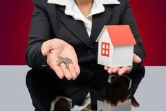 Donna di affari che tiene una casa e una chiave di modello Immagini Stock