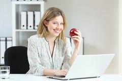 Donna di affari che tiene una mela che vi esamina l'ufficio Fotografia Stock Libera da Diritti