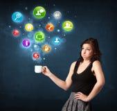 Donna di affari che tiene una tazza bianca con le icone della regolazione Immagini Stock