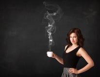 Donna di affari che tiene una tazza piena di vapore bianca Immagini Stock