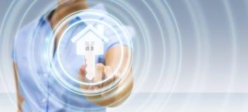 Donna di affari che tocca la casa dell'icona della rappresentazione 3D con il suo dito Fotografia Stock