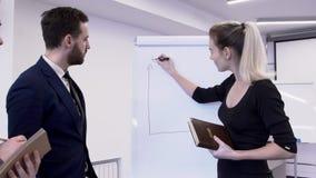 Donna di affari che traccia una carta sulla lavagna per i colleghi maschii in ufficio stock footage