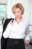 Donna di affari che trasporta il suo rivestimento sulla spalla fotografia stock libera da diritti