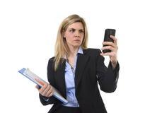Donna di affari che usando Internet app sulla cartella dell'ufficio della tenuta del telefono cellulare e penna che sembra occupa Immagine Stock Libera da Diritti