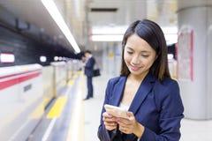 Donna di affari che utilizza cellulare nel binario del treno immagini stock