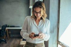 Donna di affari che utilizza il suo Smart Phone nell'ufficio fotografie stock libere da diritti