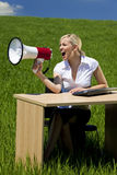 Donna di affari che utilizza megafono in un campo verde Immagini Stock