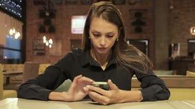 Donna di affari che utilizza smartphone nel caffè video d archivio