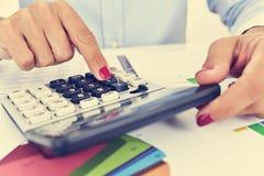 Donna di affari che utilizza una calcolatrice elettronica nel suo ufficio Immagini Stock Libere da Diritti