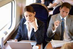 Donna di affari Commuting To Work sul treno e sul computer portatile usando Immagini Stock Libere da Diritti