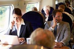 Donna di affari Commuting To Work sul treno e sul computer portatile usando fotografia stock libera da diritti