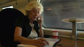 Donna di affari Commuting To Work sul treno facendo uso del telefono cellulare video d archivio