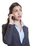 Donna di affari con capelli marroni lunghi che ascolta al telefono Fotografie Stock