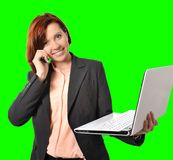 Donna di affari con capelli rossi che parla sul computer portatile mobile della tenuta del telefono cellulare a disposizione isol Immagine Stock