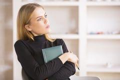 Donna di affari con il blocco note che pensa nel luogo di lavoro immagine stock libera da diritti