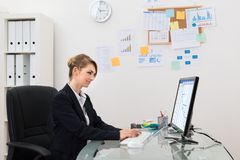Donna di affari con il calcolatore in ufficio fotografie stock