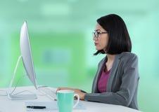 Donna di affari con il computer allo scrittorio con fondo verde intenso Immagine Stock