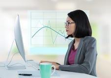 Donna di affari con il computer allo scrittorio con il grafico del diagramma Fotografia Stock Libera da Diritti