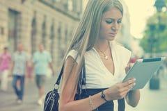 Donna di affari con il computer della compressa che cammina sulla via urbana immagine stock libera da diritti
