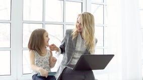 Donna di affari con il computer portatile e la bambina con la compressa che si siede dalla grande finestra fotografie stock libere da diritti