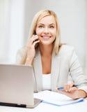 Donna di affari con il computer portatile ed il telefono cellulare Fotografia Stock