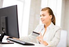 Donna di affari con il computer portatile facendo uso della carta di credito Immagini Stock