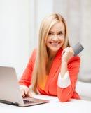 Donna di affari con il computer portatile facendo uso della carta di credito Fotografie Stock Libere da Diritti