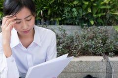 Donna di affari con il grafico finanziario che si siede fuori del buildi dell'ufficio Fotografia Stock