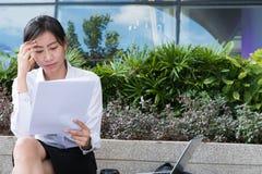 Donna di affari con il grafico finanziario che si siede fuori del buildi dell'ufficio Immagine Stock Libera da Diritti