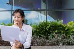 Donna di affari con il grafico finanziario che si siede fuori del buildi dell'ufficio Fotografie Stock Libere da Diritti
