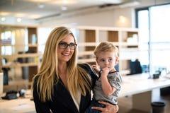 Donna di affari con il piccolo bambino nell'ufficio Fotografie Stock Libere da Diritti