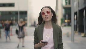 Donna di affari con il telefono che cammina nella via vaga e nel sorridere della città stock footage