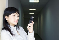 Donna di affari con il telefono in corridoio Fotografia Stock