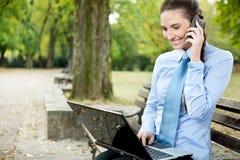 Donna di affari con il telefono ed il computer portatile Fotografie Stock Libere da Diritti