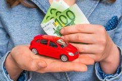 Donna di affari con l'automobile rossa del giocattolo e dei soldi in mani Fotografia Stock
