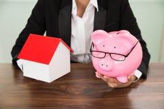 Donna di affari con la casa ed il porcellino salvadanaio Immagine Stock Libera da Diritti